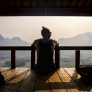 person of a group of yoga practicioners sitting outside and watching into landscape of mountains